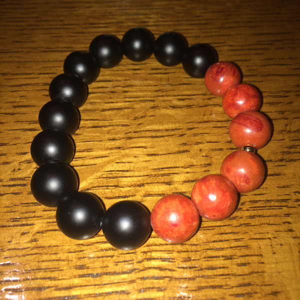 Ngao Brown Boy Bad Bracelet-- red and black beads on a wood table